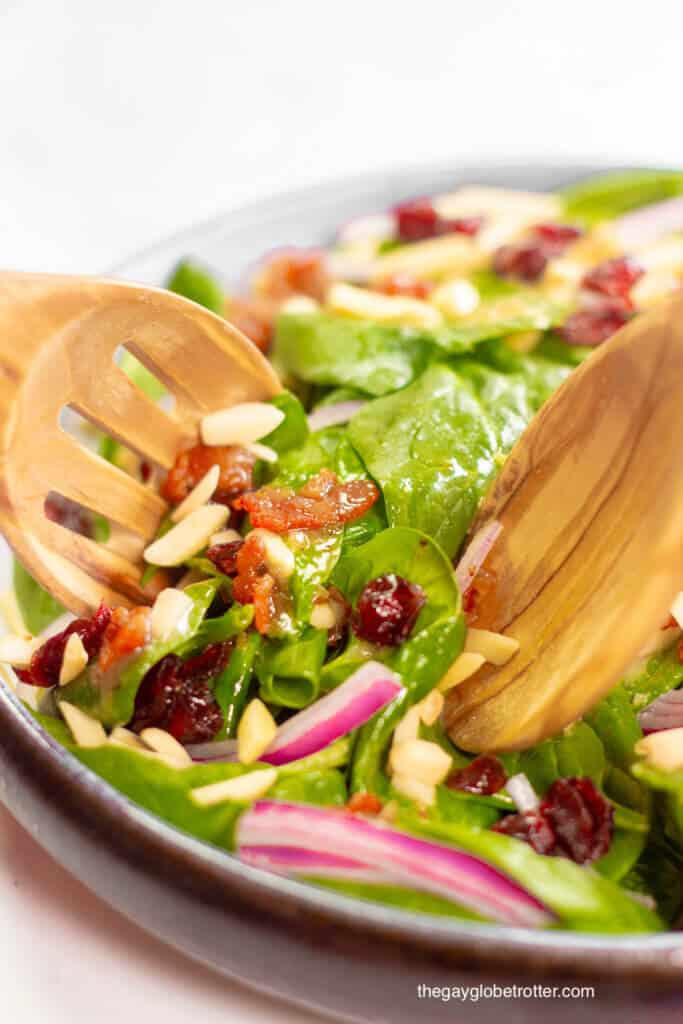 Serving utensils tossing spinach cranberry salad and warm bacon dressing.