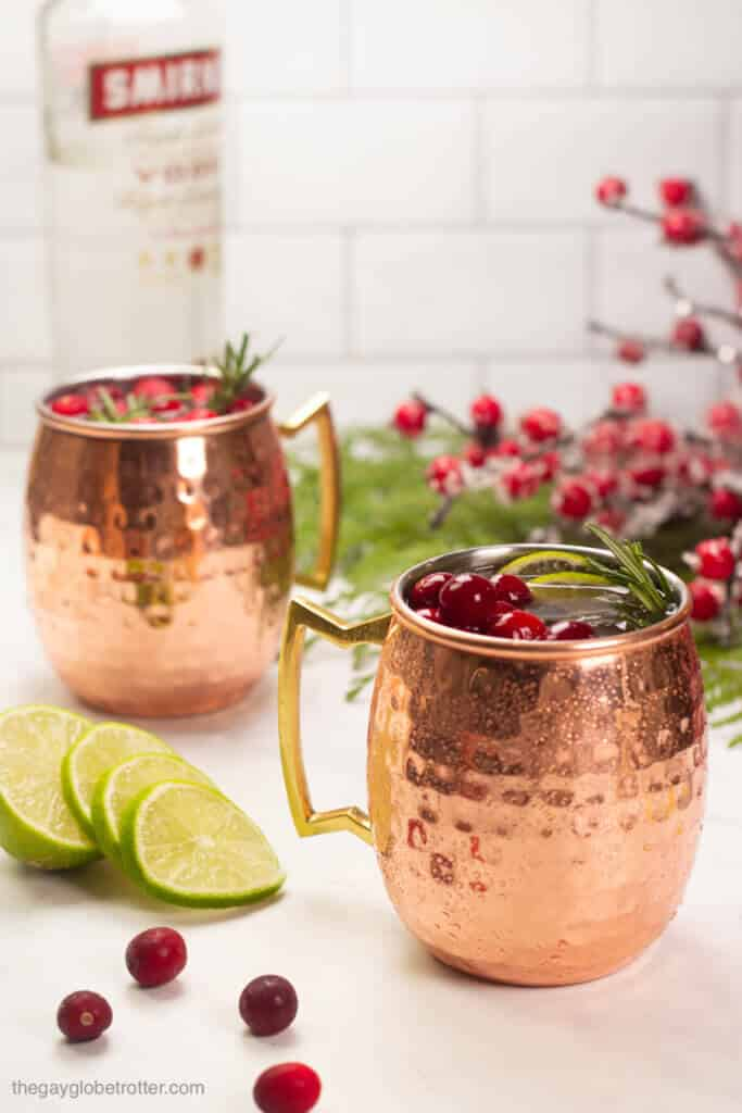 Two cranberry moscow mules next to a bottle of vodka.