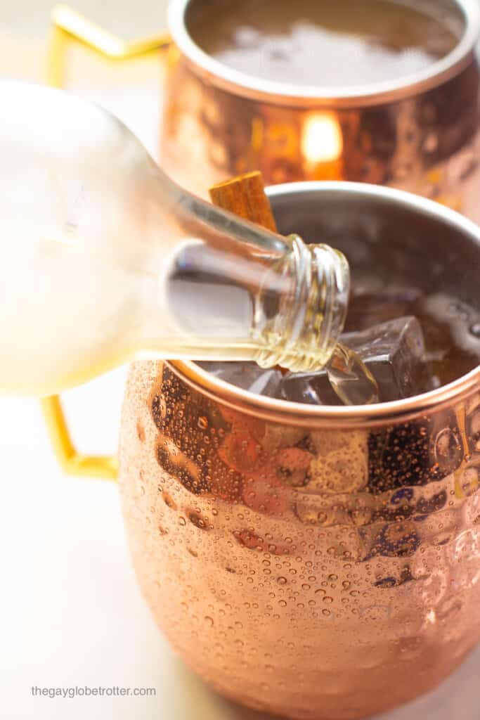 Ginger beer being poured into a copper mug for moscow mules.