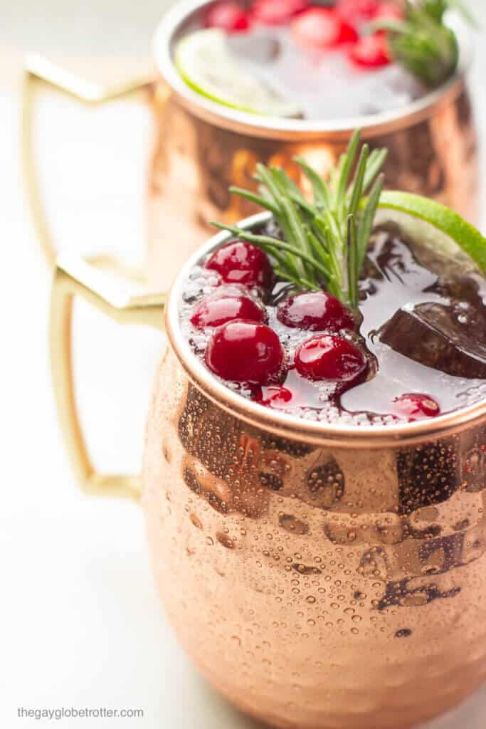 A close up of a cranberry moscow mule garnished with lime, cranberries, and fresh rosemary.