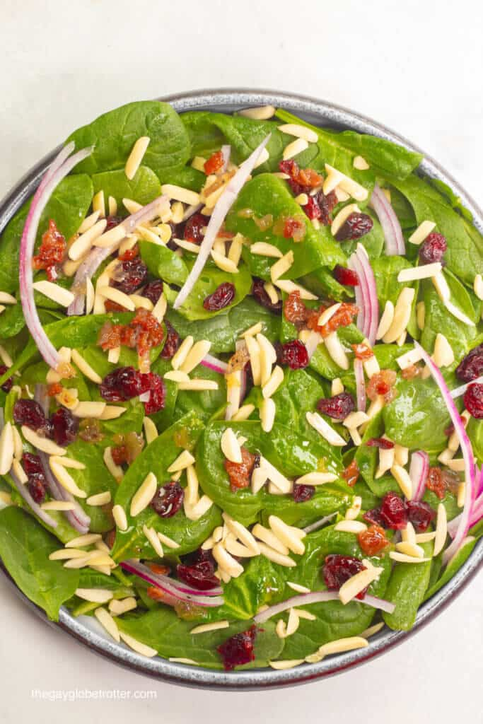 A bowl of spinach cranberry salad ready to be dressed.