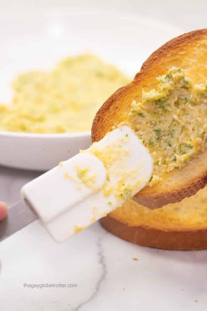 Roasted garlic butter being smeared on a slice of toasted bread.