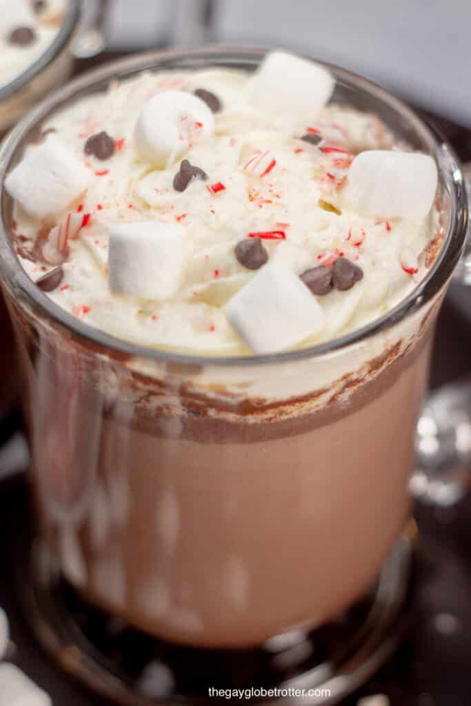 A close up of hot chocolate with candy cane pieces, chocolate chips, marshmallows, and whipped cream.