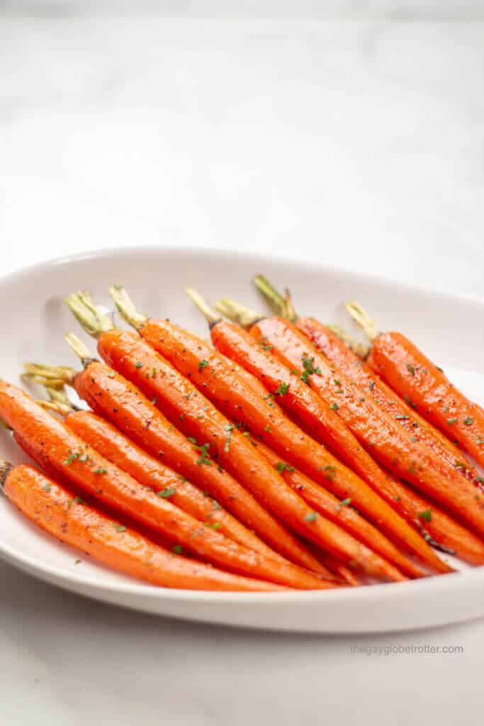 Honey glazed carrots garnished with parsley in a serving dish.