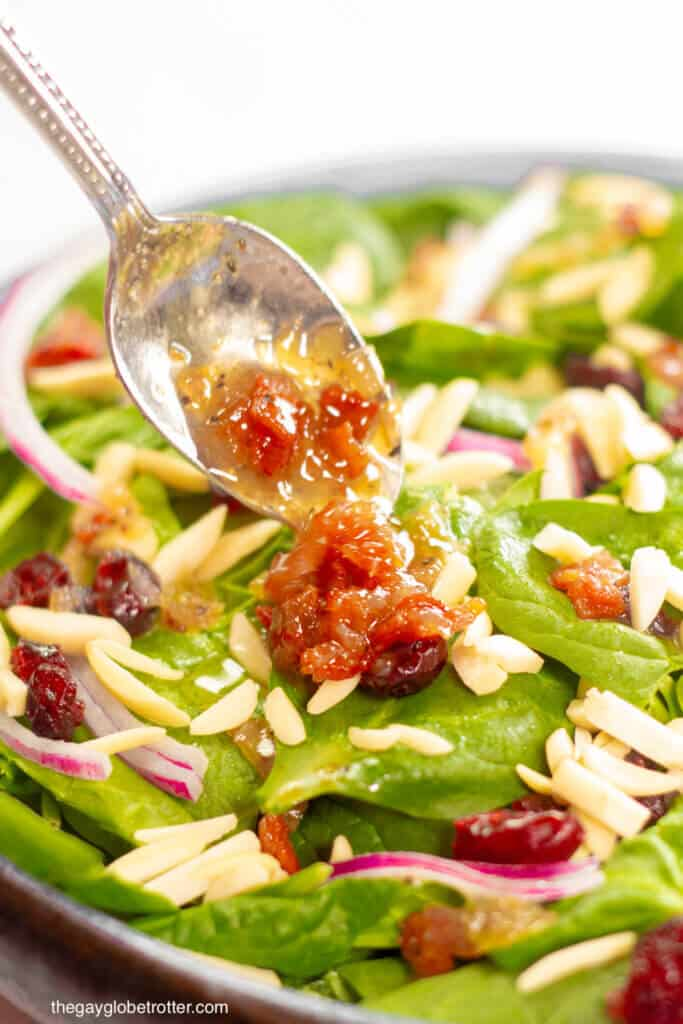 A spoon adding warm bacon dressing to spinach cranberry salad.