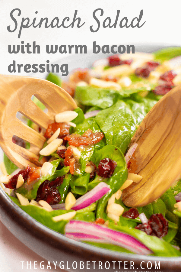 Salad being tossed in a serving dish with warm bacon dressing.