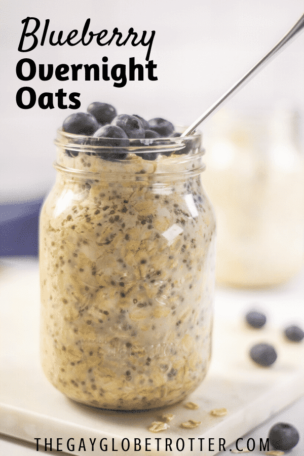 A jar of blueberry overnight oats topped with fresh blueberries and a spoon.