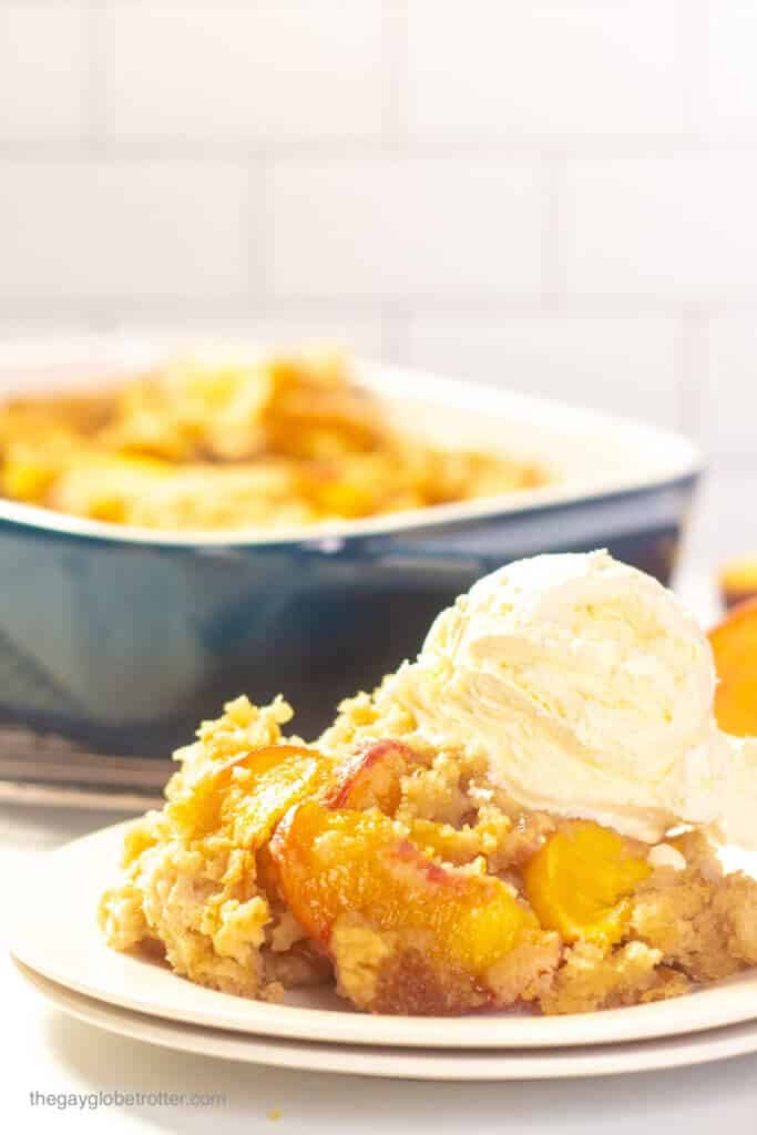 A serving of Bisquick peach cobbler on a plate with a scoop of vanilla ice cream.