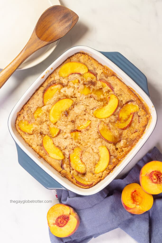 Bisquick peach cobbler in a casserole dish fresh from the oven.
