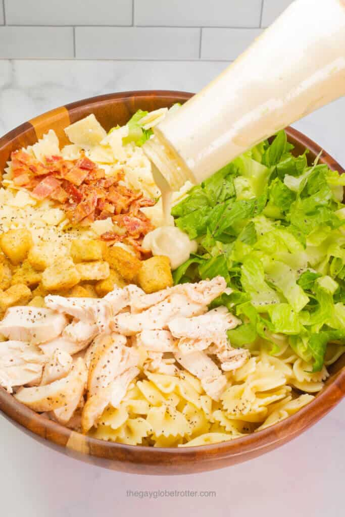 Caesar dressing being poured over caesar pasta salad ingredients.