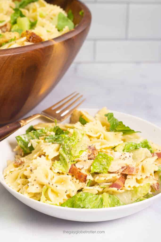 A white bowl full of chicken caesar pasta salad with a fork.