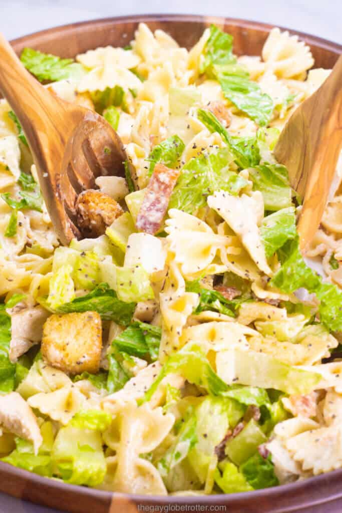 Wooden salad spoons tossing caesar pasta salad. together in a serving bowl.