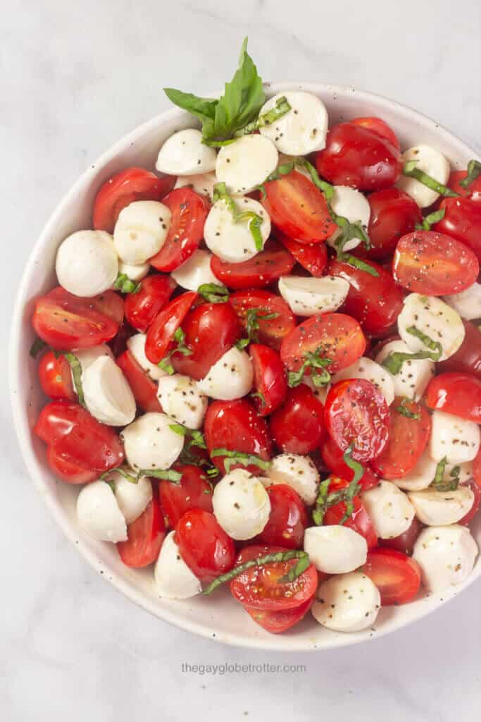 Cherry tomato caprese salad garnished with fresh basil.