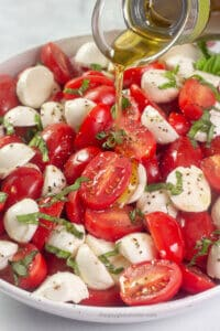 Olive oil being drizzled on cherry tomato caprese salad.