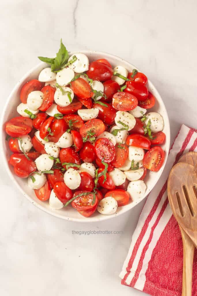 Caprese salad next to serving spoons on a cloth napkin.