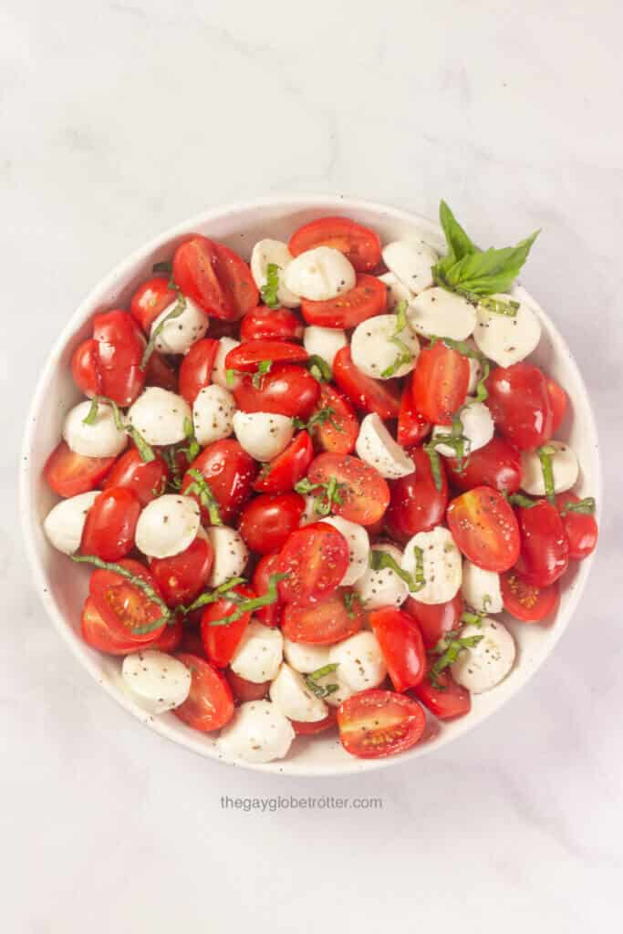 A bowl of caprese salad with fresh basil garnish.