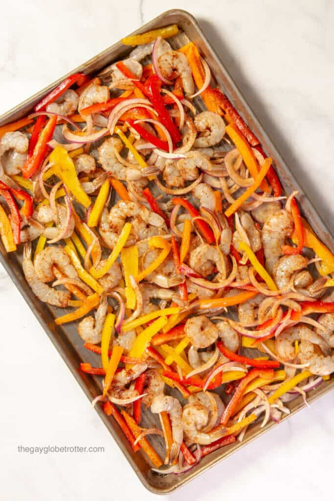 Shrimp, peppers, and onions on a baking sheet.