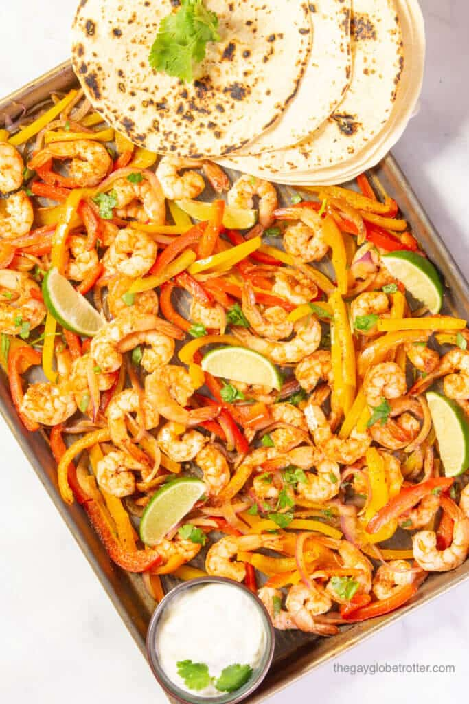 Sheet pan shrimp fajitas with lime wedges, tortillas, and sour cream.