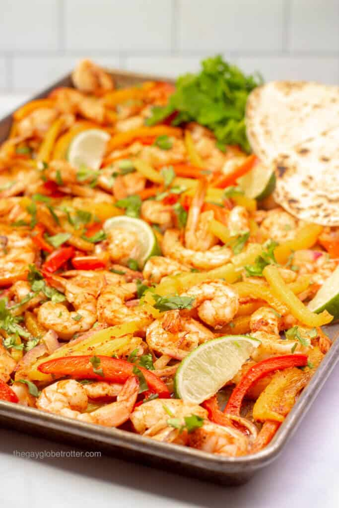 Shrimp fajitas being served on a baking sheet with cilantro, limes, and tortillas.