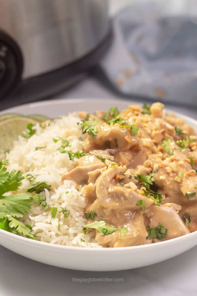 A bowl of thai peanut chicken served over coconut rice with limes and cilantro.