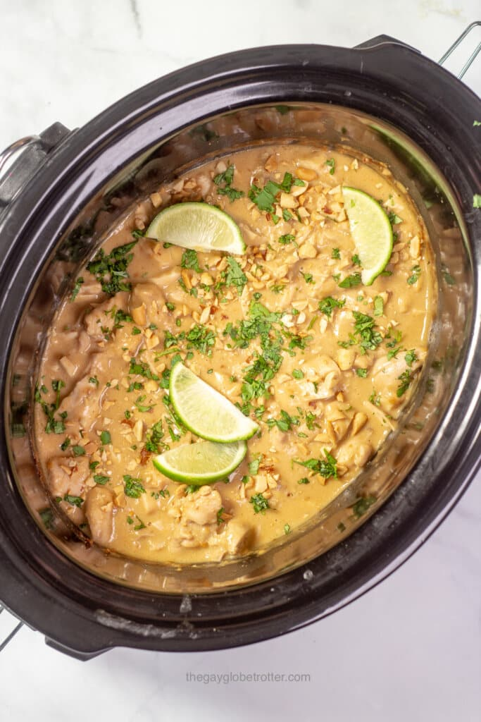 A slow cooker filled with thai peanut chicken garnished with limes, cilantro, and peanuts.