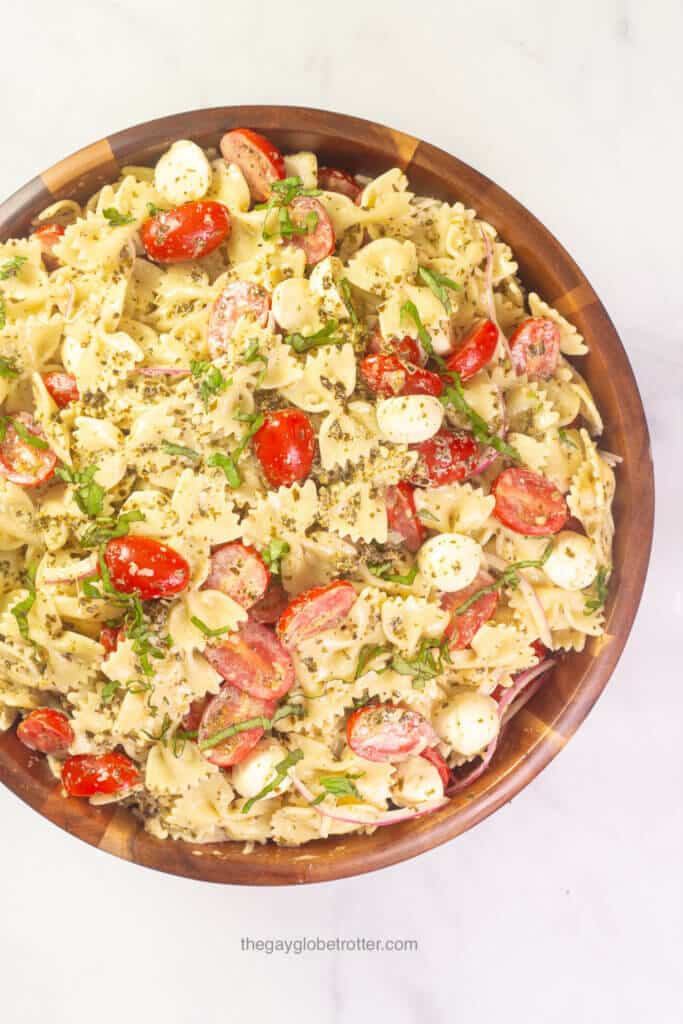 A wooden serving bowl of caprese pesto pasta salad with tomatoes, basil, and bocconcini.