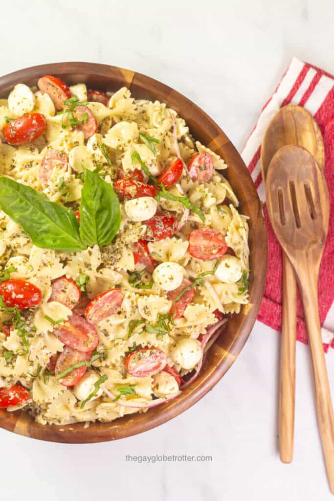 Caprese pesto pasta salad in a wood serving bowl with wooden salad spoons.