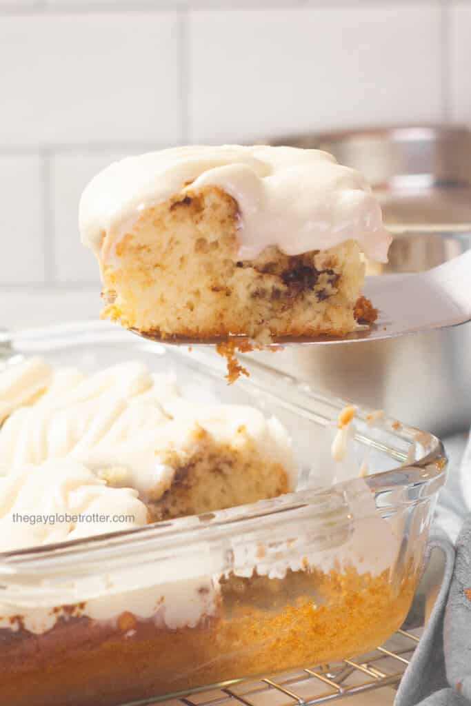 A spatula lifting cinnamon roll cake out of a clear baking dish.