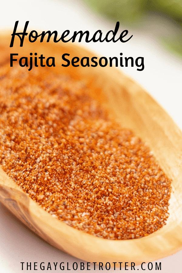 "Fajita seasoning in a wooden dish with text overlay that says ""homemade fajita seasoning"""