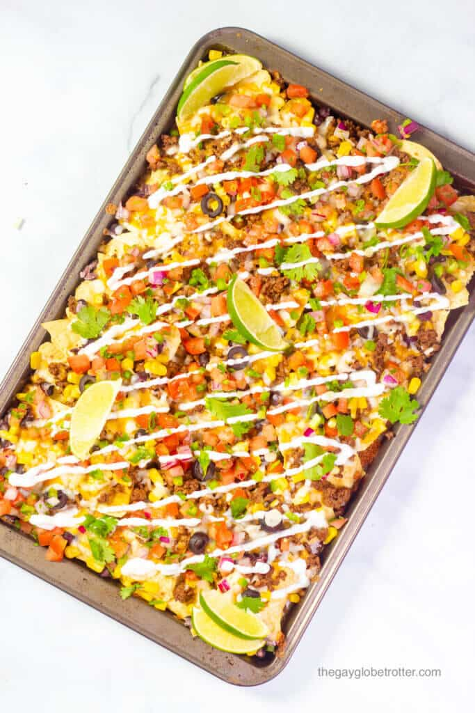 A baking sheet of loaded nachos topped with lime wedges, sour cream, and cilantro.