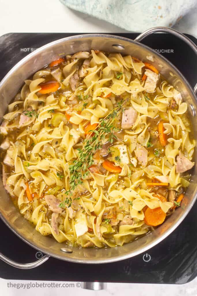 A pot of turkey noodle soup garnished with thyme.