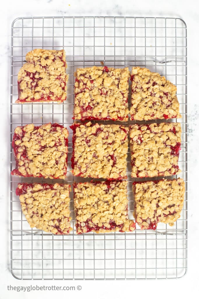 Raspberry oatmeal bars cut into squares on a cooling rack.