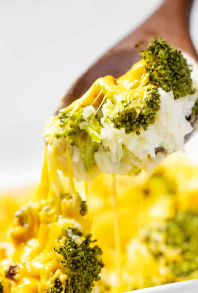 A spoon serving cheesy broccoli and rice casserole.