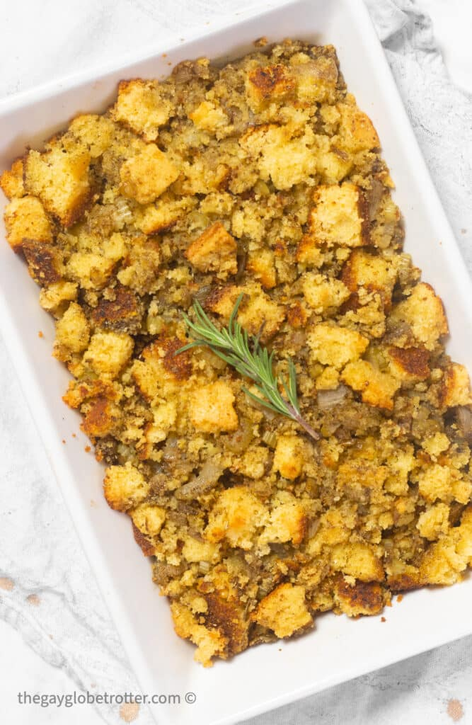 Cornbread stuffing in a serving dish garnished with rosemary.