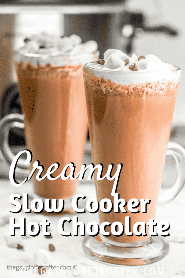 CrockPot hot chocolate in a clear glass with whipped cream and marshmallows.