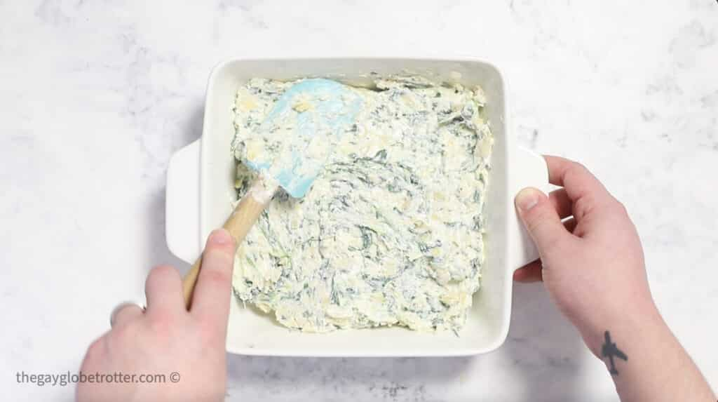 Spinach artichoke dip being spread into a baking dish with a spatula.