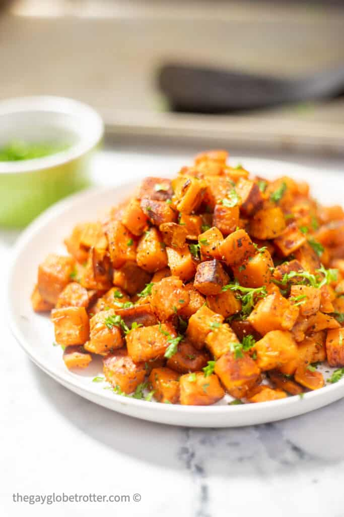 Roasted sweet potatoes on a plate with fresh parsley.