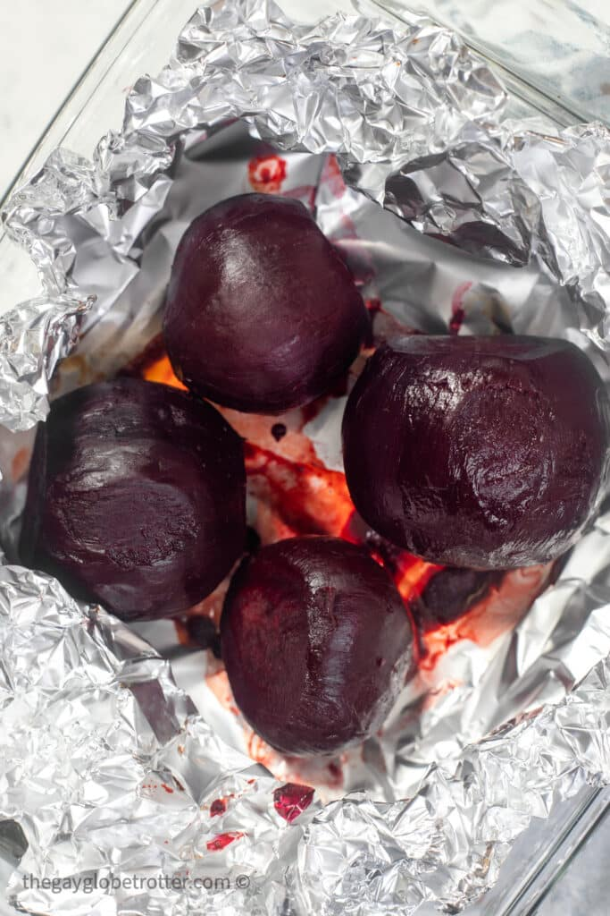 Peeled whole roasted beets in foil in a clear baking dish.
