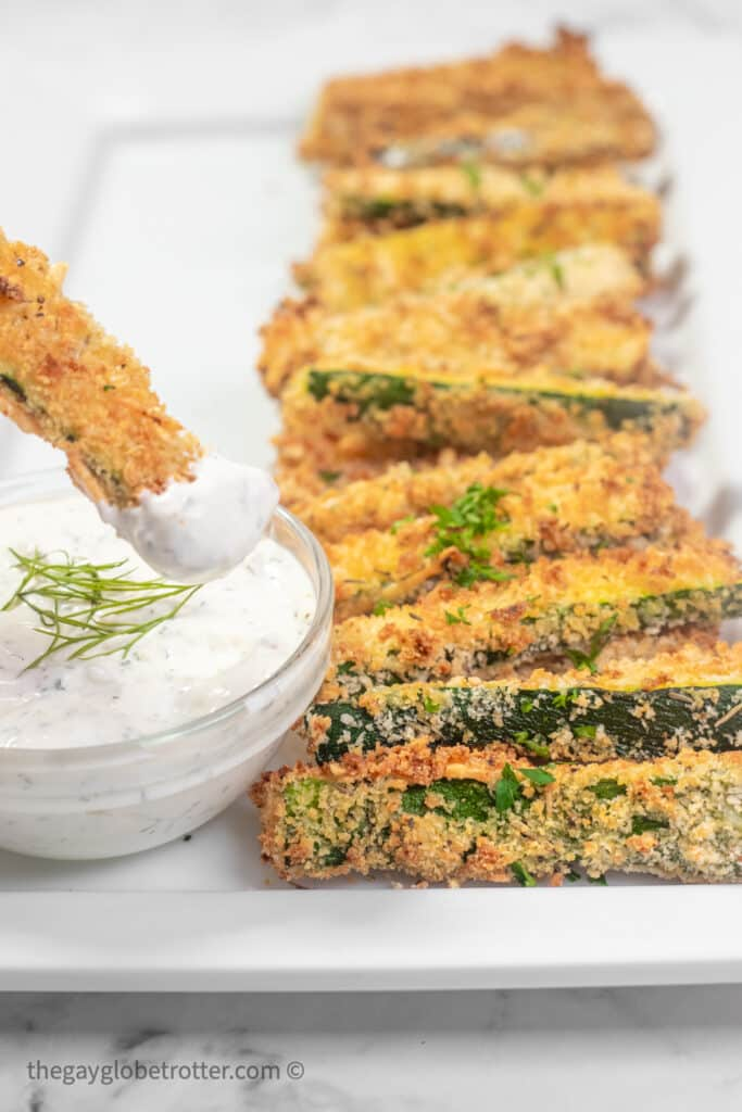 A breaded zucchini stick being dipped into creamy dill dip.