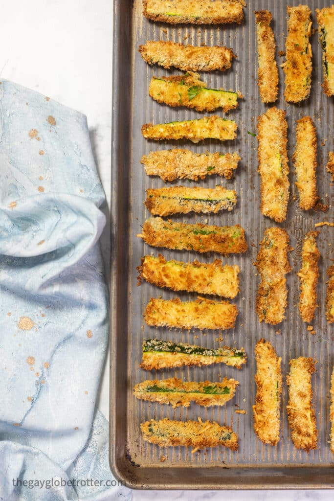 A baking sheet with baked zucchini sticks next to a tea towel.
