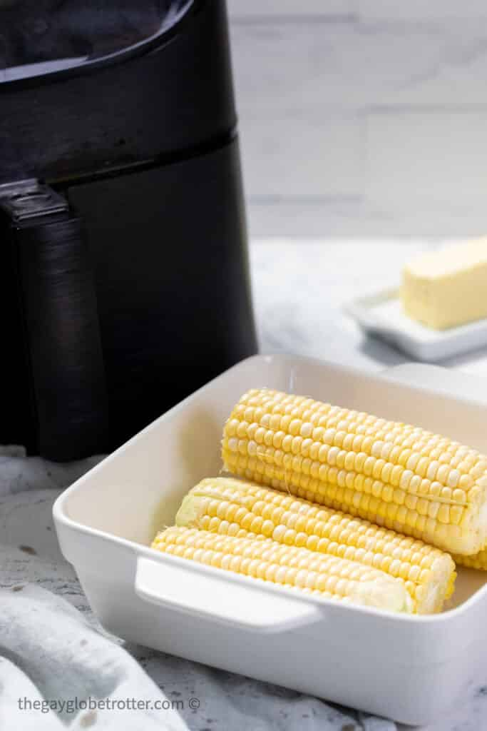 Raw corn in a dish next to an air fryer.