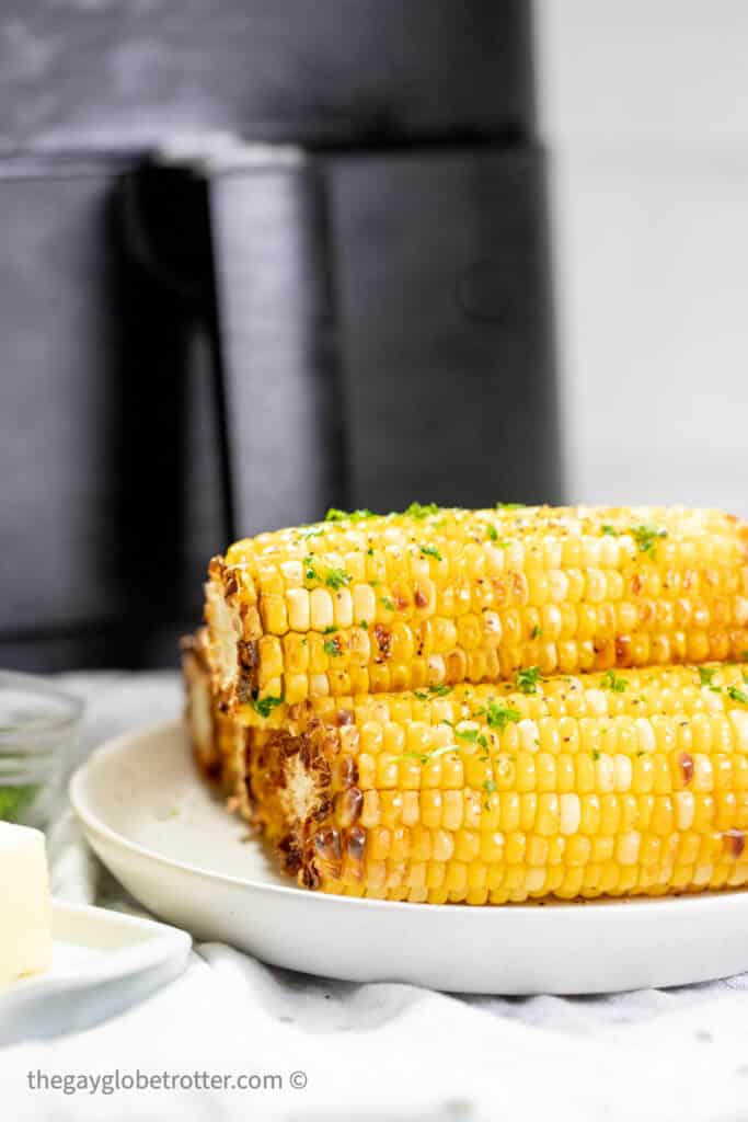 Corn on the cob on a plate next to an air fryer.