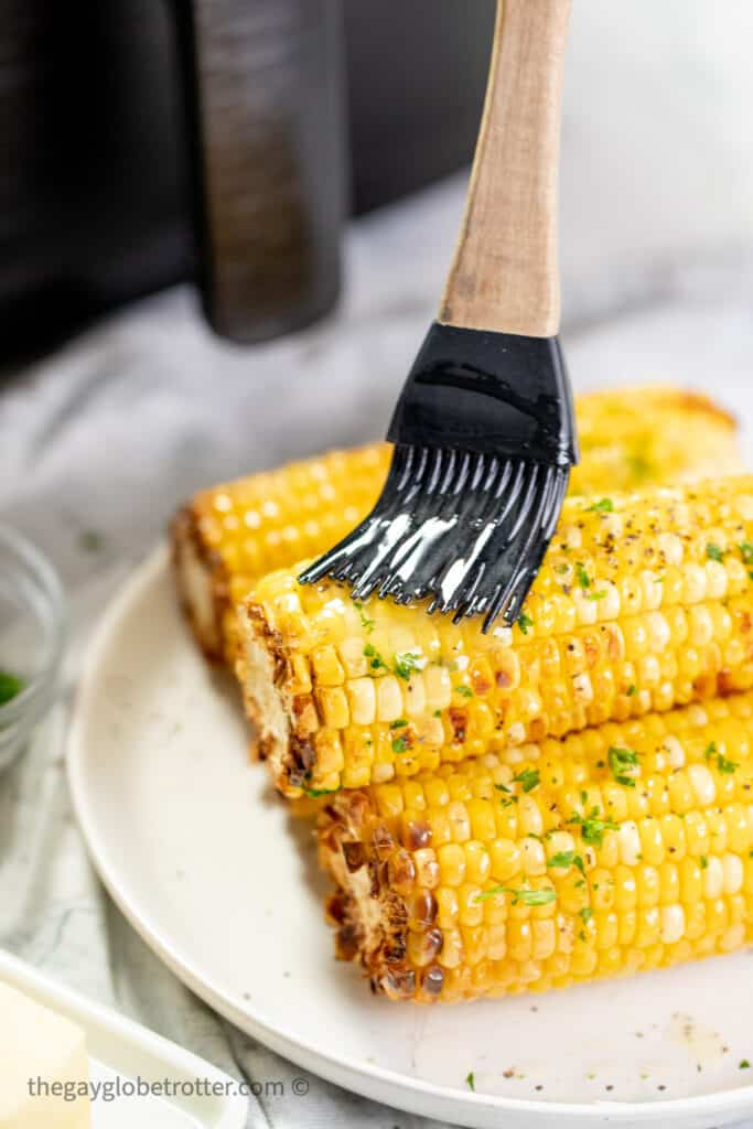Butter being brushed onto corn on the cob.