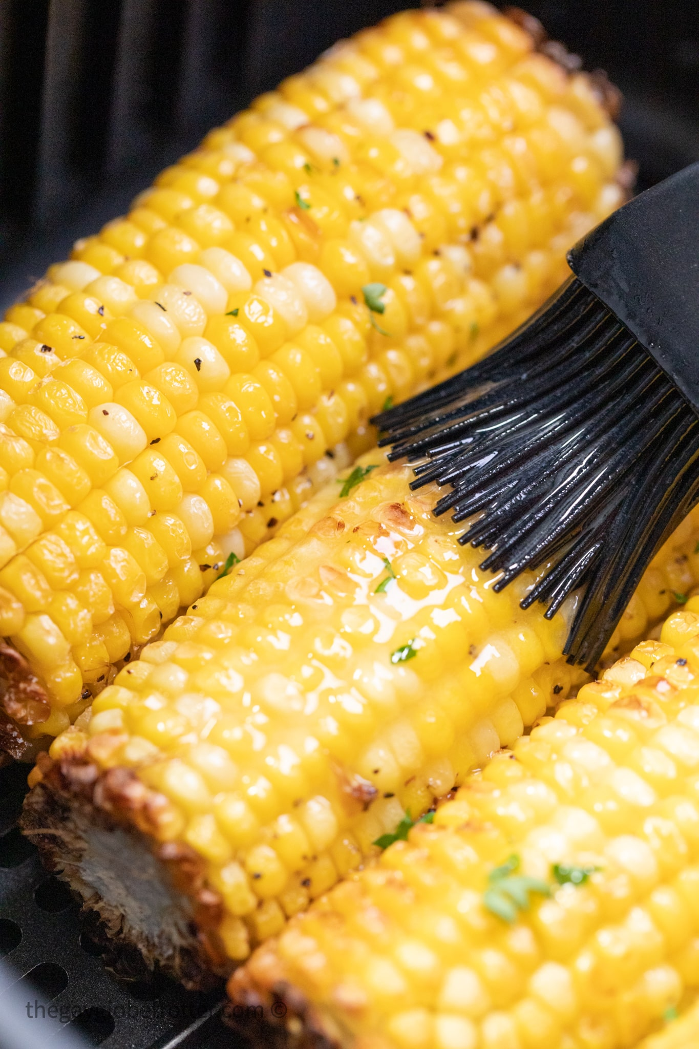 Butter bing brushed on corn in the air fryer.
