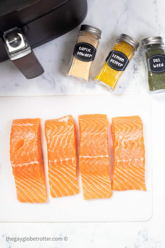 Raw salmon next to spices and an air fryer.