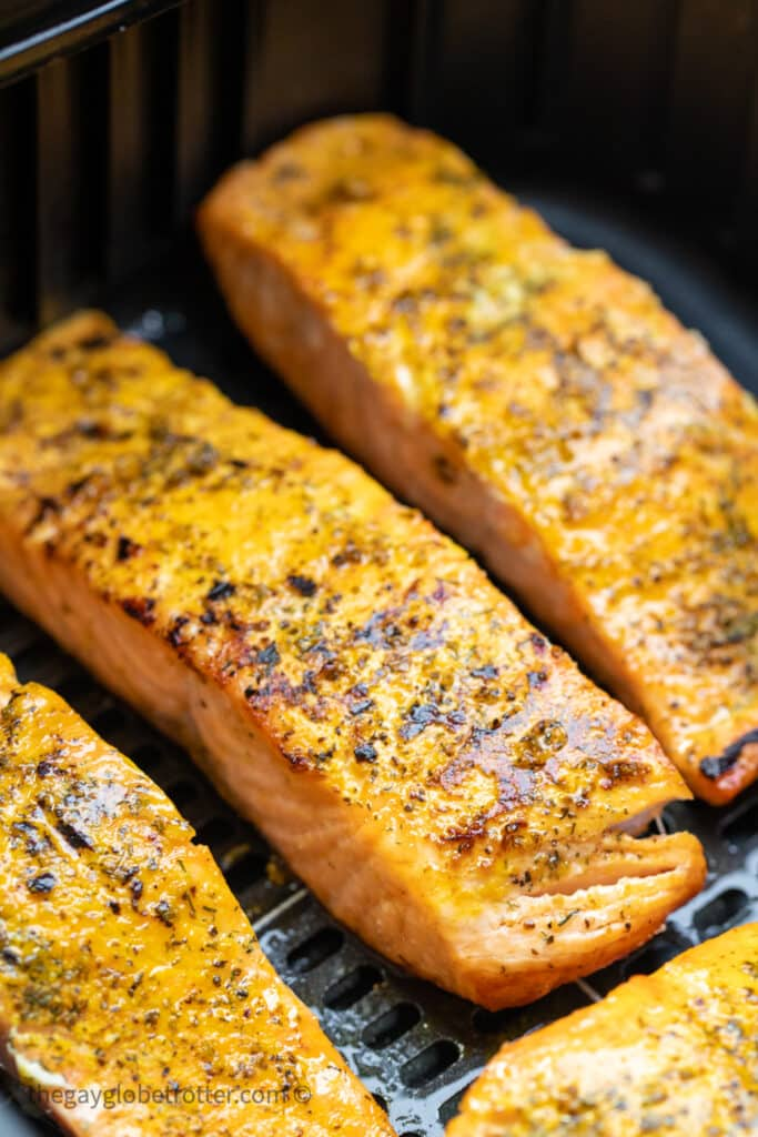 Cooked salmon in an air fryer basket.