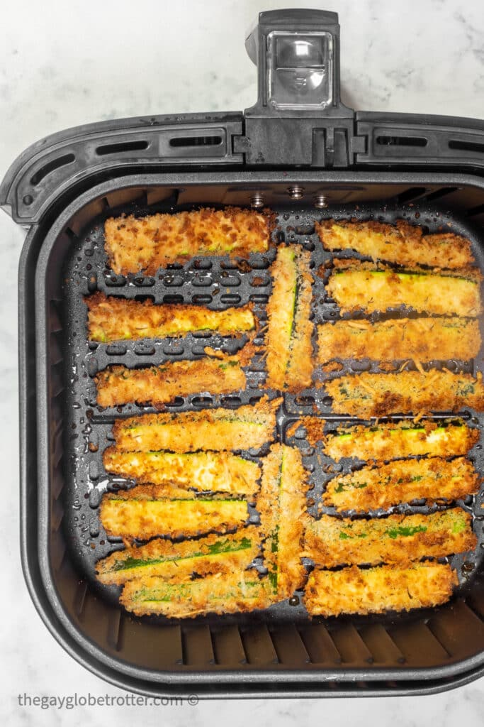 Cooked zucchini fries in an air fryer basket.