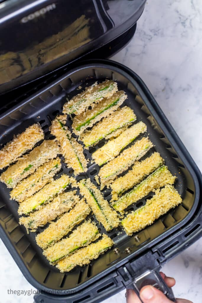 Zucchini fries in an air fryer basket being placed into an air fryer.