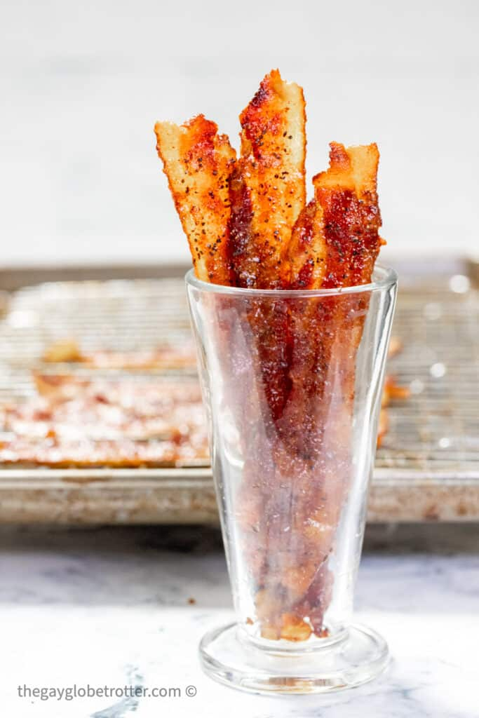 A cup of candied bacon next to a baking sheeet.