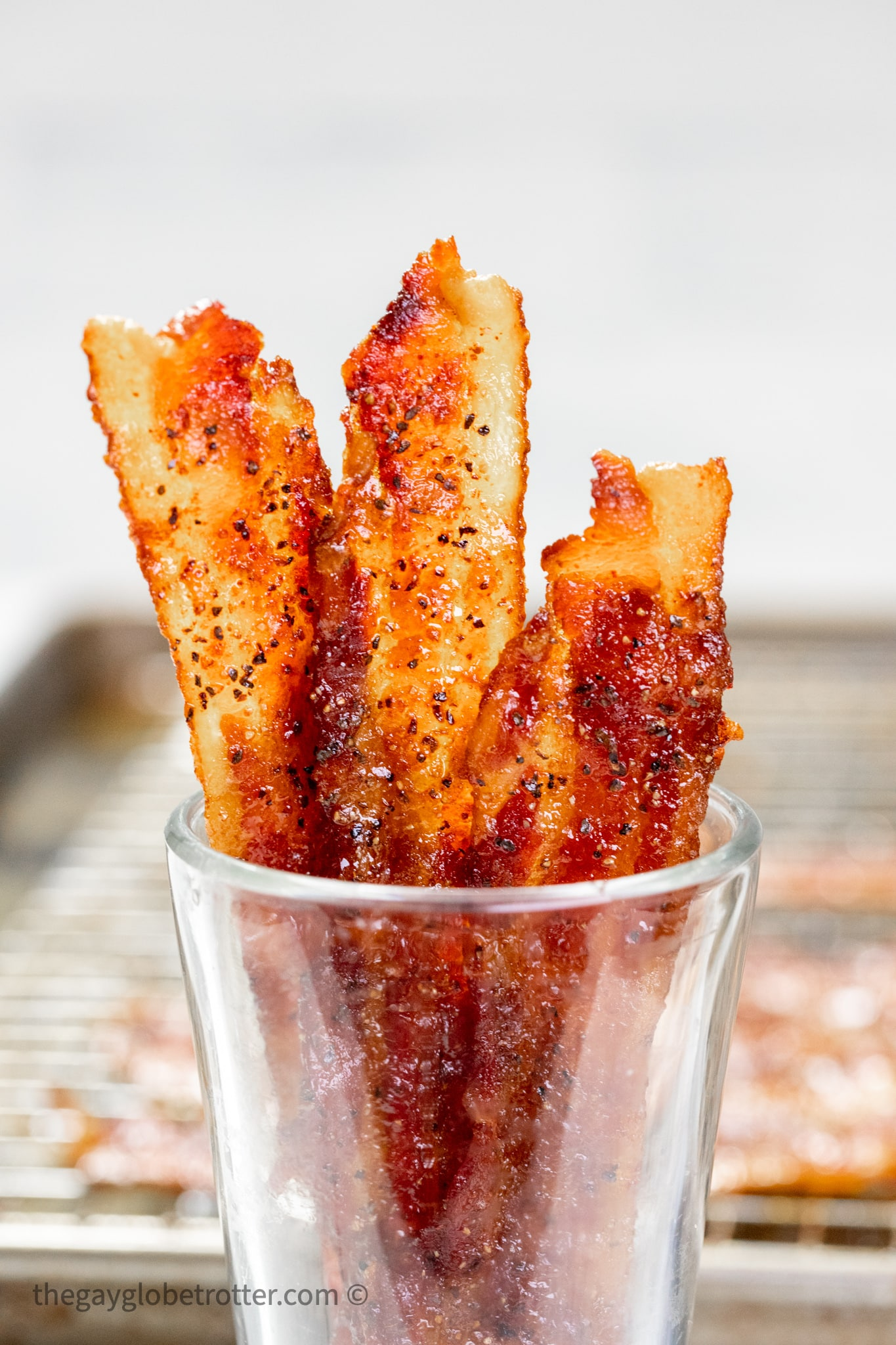 Candied bacon in a clear cup.